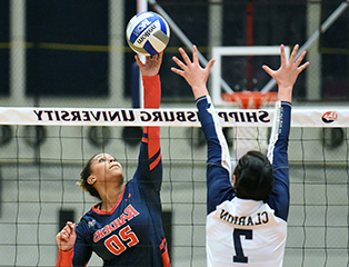 mg游戏app volleyball player leaping to reach ball above net in gymnasium while another woman attempts to block it.