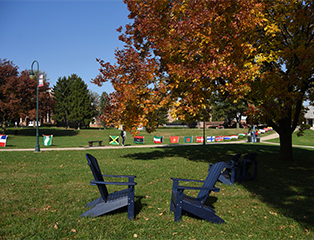 Two adirondack chairs on the campus of mg游戏app with trees, flags and students walking in the background.
