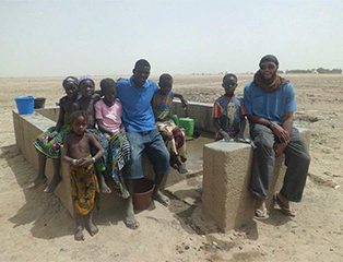 Man and several children sitting at water pump in Mali.