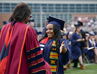 Female student preparing to hug mg游戏app president Laurie Carter at commencement ceremony.